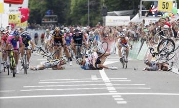 The pack of riders crashes next to the finish line during the fourth stage of the Tour de Suisse in Wettingen